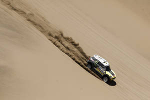 "Photo - Mini driver Joan ""Nani"" Roma of Spain and co-pilot Michel Perin of France race down a dune during the ninth stage of the Dakar Rally between the cities of Calama and Iquique, Chile, Tuesday, Jan. 14, 2014. (AP Photo/Victor R. Caivano)"