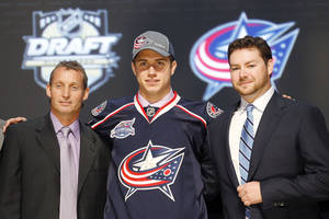 Photo -   Ryan Murray , center, a defenseman, stands with officials from the Columbus Blue Jackets after being chosen second overall in the first round of the NHL hockey draft on Friday, June 22, 2012, in Pittsburgh. (AP Photo/Keith Srakocic)