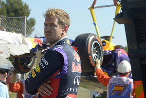 Photo - Red Bull driver Sebastian Vettel of Germany looks around as his car is taken away after he lost control  during a first free practice session at the Barcelona Catalunya racetrack in Montmelo, near Barcelona, Spain, Friday, May 9, 2014. The Formula One race will be held on Sunday. (AP Photo/Manu Fernandez)