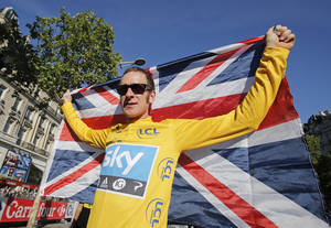 Photo - Bradley Wiggins, winner of the 2012 Tour de France, holds the Union flag aloft during a parade after the last stage of the race on Sunday. AP Photo