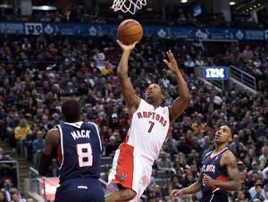 Photo - Toronto Raptors guard Kyle Lowry (7) scores past Atlanta Hawks teammates Shelvin Mack (8) and Jeff Teague, right, during the first half of an NBA basketball game in Toronto on Sunday, March 23, 2014. (AP Photo/The Canadian Press, Nathan Denette)