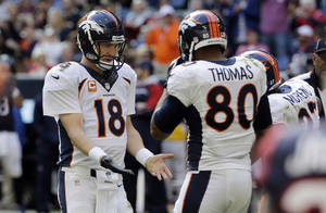 Photo - Denver Broncos' Peyton Manning (18) celebrates with Julius Thomas (80) and other teammates after throwing a pass for a touchdown against the Houston Texans during the third quarter of an NFL football game on Sunday, Dec. 22, 2013, in Houston. (AP Photo/David J. Phillip)