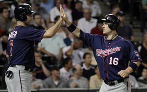 Photo -   Minnessota Twins' Josh Willingham, right, gets a high-five from Joe Mauer as Willingham scores during the fifth inning of a baseball game against the Chicago White Sox, Tuesday, Sept. 4, 2012, in Chicago. (AP Photo/John Smierciak)