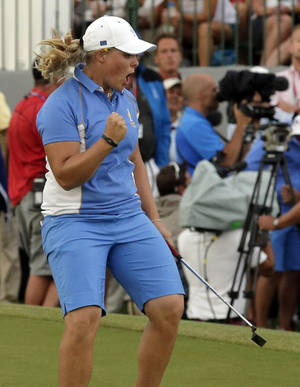 Photo - Europe's Caroline Hedwall from Sweden reacts after making a birdie putt on the 18th hole to give her the win over United States' Michelle Wie  during the singles matches at the Solheim Cup golf tournament Sunday, Aug. 18, 2013, in Parker, Colo. The win gave Europe 14 points and they retained the Solheim Cup. (AP Photo/Chris Carlson)