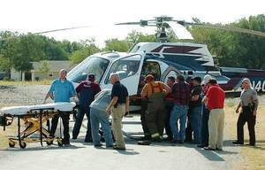 photo - Emergency responders load an injured teen into an awaiting air ambulance at Zaloudek Grain Company in Kremlin, Okla. Thursday, August 4, 2011. Tyler Zander and Bryce Gannon, both 17, were extricated from a grain auger and taken by Eagle-Med helicopter to OU Medical Center in Oklahoma City with leg injuries. Photo by Cass Rains/Enid News &amp; Eagle ORG XMIT: KOD