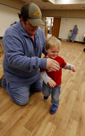 Photo -  Brandon Thompson and son Warren, 2, do the Chicken Dance during a family dance party at the Norman Public Library. Photo by Steve Sisney, The Oklahoman  <strong>STEVE SISNEY -   </strong>