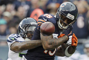 Photo - Chicago Bears wide receiver Brandon Marshall (15) fumbles after getting hit by Seattle Seahawks cornerback Brandon Browner (39) in the first half of an NFL football game in Chicago, Sunday, Dec. 2, 2012. Marshall recovered his own fumble.  (AP Photo/Nam Y. Huh)