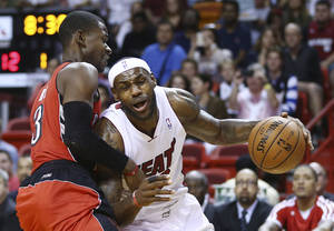 Photo - Miami Heat's LeBron James (6) drives around Toronto Raptors' Terrence Ross (31) during the first half of an NBA basketball game, Sunday, Jan. 5, 2013, in Miami. (AP Photo/J Pat Carter)