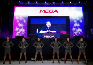 "Photo - Indicted Megaupload founder Kim Dotcom appears on a large screen during the launch of a new file-sharing website called ""Mega"" at his Coatesville mansion in Auckland, New Zealand, Sunday, Jan. 20, 2013. The colorful entrepreneur unveiled the site ahead of a lavish gala and press conference on the anniversary of his arrest on racketeering charges related to his now-shuttered Megaupload file-sharing site. (AP Photo/New Zealand Herald, Richard Robinson) New Zealand Out, Australia Out"