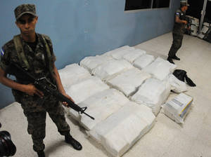 Photo - Marines belonging to the Honduras Navy stand guard next to 772 pounds (350 kilograms) of cocaine at the naval base in Tegucigalpa, Honduras, Wednesday, Jan 16, 2013. A Jamaican man suspected of drug trafficking has died in the first Honduran anti-narcotics raid on a small boat about 2.5 miles (4 kms) off Honduras' northern coast using U.S. intelligence following a five-month suspension of radar sharing. Another man of Jamaican nationality was arrested. (AP Photo/Fernando Antonio)