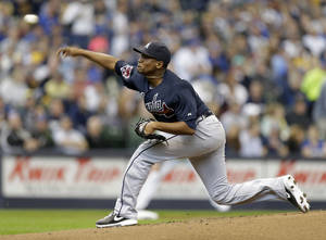 Photo - Atlanta Braves starting pitcher Julio Teheran throws to the Milwaukee Brewers in the first inning of an opening day baseball game Monday, March 31, 2014, in Milwaukee. (AP Photo/Jeffrey Phelps)