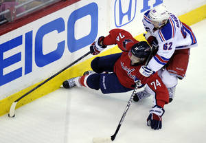 Photo -   Washington Capitals defenseman John Carlson (74) tries to keep control of the puck under pressure from New York Rangers left wing Carl Hagelin (62) during the second period of Game 3 of their NHL hockey Stanley Cup second-round playoff series at the Verizon Center in Washington, Wednesday, May 2, 2012. (AP Photo/Susan Walsh)