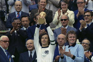 "Photo - FILE - In this July 7, 1974 file photo, West Germany captain, Franz Beckenbauer, holds up the World Cup trophy after his team defeated the Netherlands by 2-1, in the World Cup soccer final at Munich's Olympic stadium, in West Germany. Applauding at right, German goalkeeper Josef ""Sepp"" Maier. On this day: West Germany wins its second World Cup after defeating the much-fancied Dutch. (AP Photo/File)"