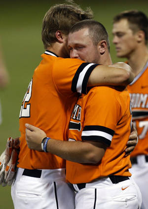 Photo - OSU's Dustin Williams (22). left, and Zach Fish (26) hug after Game 2 of the NCAA baseball Stillwater Super Regional between Oklahoma State and UC Irvine at Allie P. Reynolds Stadium in Stillwater, Okla., Saturday, June 7, 2014. UC Irvine won 1-0. Photo by Nate Billings, The Oklahoman