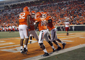 Photo - Oklahoma State celebrates a touchdown on a blocked punt during a college football game between Oklahoma State University and the Texas Tech University (TTU) at Boone Pickens Stadium in Stillwater, Okla., Saturday, Nov. 17, 2012. Photo by Sarah Phipps, The Oklahoman