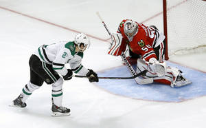 Photo - Dallas Stars left wing Antoine Roussel, left, shoots and scores past Chicago Blackhawks goalie Corey Crawford on a penalty shot during the third period of an NHL hockey game Tuesday, Dec. 3, 2013, in Chicago. Dallas won 4-3. (AP Photo/Charles Rex Arbogast)