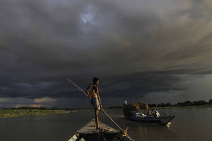 Photo -   A boat carries flood relief materials as monsoon clouds surrounded the flood affected Gagalmari village in Assam state, India, Monday, July 2, 2012. The floods from monsoon rains in northeastern India killed dozens of people, with more than 2,000 villages inundated as rivers breached their banks, an official said Sunday. (AP Photo/Anupam Nath)