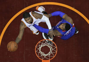 Photo - Cleveland Cavaliers' Kyrie Irving, left, shoots against Detroit Pistons' Andre Drummond during the first quarter of an NBA basketball game Monday, Dec. 23, 2013, in Cleveland. (AP Photo/Mark Duncan)