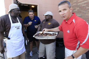 Photo -   Michigan head football coach Brady Hoke, second from left, and Ohio State head football coach Urban Meyer, right, sample ribs from Gerald Wright, left, and Derrick McCray at the eighth annual Sound Mind, Sound Body Football Academy at the Southfield High School in Southfield, Mich., Wednesday, June 13, 2012. Meyer and Hoke were two of a handful of college coaches who were on hand at the camp, which draws kids from all over the country. (AP Photo/Carlos Osorio)