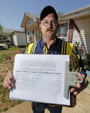Photo - Bobby Burgess holds a petition at his home in Valley Brook, Friday April 19, 2013. Residents are uneasy about sex offenders living in the area. Photo By Steve Gooch, The Oklahoman ORG XMIT: OKC1303121532440650