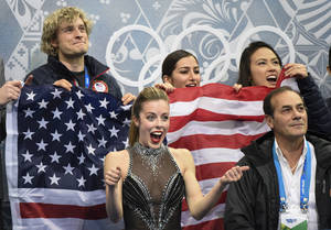 Photo - Ashley Wagner from the United States, surrounded by teammates reacts to her marks after competing in the women's team short program figure skating competition at the Iceberg Skating Palace during the 2014 Winter Olympics, Saturday, Feb. 8, 2014, in Sochi, Russia.  (AP Photo/The Canadian Press, Paul Chiasson)