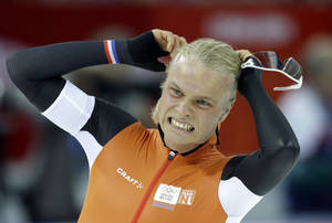 Photo - Silver medalist Koen Verweij of the Netherlands grabs his hair when the race was declared a tie with gold medalist Poland's Zbigniew Brodka  in the men's 1,500-meter speedskating race at the Adler Arena Skating Center during the 2014 Winter Olympics in Sochi, Russia, Saturday, Feb. 15, 2014. Verweij later was later declared silver, losing by three thousandth of a second. (AP Photo/Patrick Semansky)