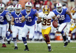 Photo - Washington Redskins running back Chris Thompson (35) rushes the ball past Buffalo Bills defenders in the second half of an NFL preseason football game Saturday, Aug. 24, 2013, in Landover, Md. (AP Photo/Nick Wass)