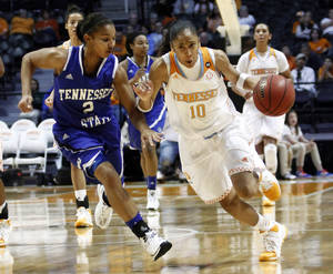 Photo - Tennessee guard Meighan Simmons (10) drives against Tennessee State guard Diamond Beatty (2) in the second half of an NCAA college basketball game Tuesday, Dec. 17, 2013, in Knoxville, Tenn. Tennessee won 94-43. (AP Photo/Wade Payne)