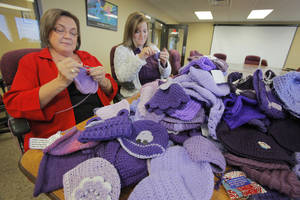 "Photo - Penny Hill-Malone and Aimee Merick crochet purple caps for the ""Click for Babies"" program to raise awareness about normal infant crying and the dangers of shaking a baby. Photo by David McDaniel, The Oklahoman"