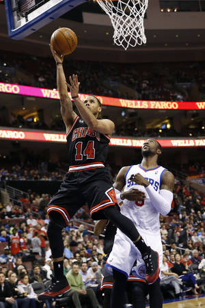 Photo - Chicago Bulls' D.J. Augustin, left, goes up for a shot as Philadelphia 76ers' Tony Wroten looks on during the first half of an NBA basketball game, Wednesday, March 19, 2014, in Philadelphia. Chicago won 102-94. (AP Photo/Matt Slocum)