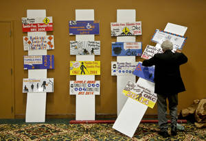 Photo - Dr. Henry Asin arranges some of the posters honored in the poster contest Tuesday during the 23rd annual Mayor's Committee on Disability Concerns awards at St. Luke's United Methodist Church. Photo by Chris Landsberger, The Oklahoman <strong>CHRIS LANDSBERGER</strong>