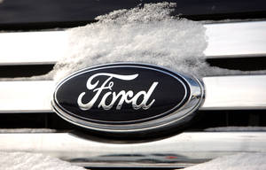 Photo - FILE - In this Sunday, Jan. 4, 2009, file photo, snow builds up on the company logo on the chromed grille of a vehicle at a Ford dealership in Denver. The federal government said Tuesday, March 4, 2014, it is closing an investigation into 1.6 million Ford vehicles that can lose engine power after Ford agreed to a remedy.  (AP Photo/David Zalubowski, File)