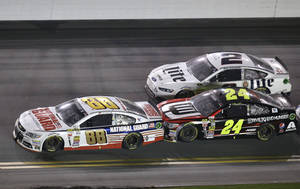 Photo - FILE - In this Feb. 23, 2014, file photo, Dale Earnhardt Jr. (88) gets a push from teammate Jeff Gordon (24) as Brad Keselowski (2) makes a run on a green flag restart on the next to last lap of the Daytona 500 NASCAR Sprint Cup Series auto race at Daytona International Speedway in Daytona Beach, Fla. Gordon and his Hendrick Motorsports teammates take up three of the top-five spots in the Sprint Cup standings. Keselowski, who picked up his third win of the season last week, is ranked third and eager to make a run at another Sprint Cup championship. It's shaping up to be a Hendrick vs. Team Penske rivalry down to the wire.   (AP Photo/John Raoux, File)