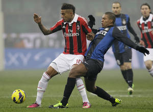 photo - AC Milan midfielder Kevin Prince Boateng, left, of Ghana, challenges for the ball with Inter Milan Brazilian defender Juan Guilherme Nunes during their Serie A soccer match, at the San Siro stadium in Milan, Italy, Sunday, Feb. 24, 2013. (AP Photo/Antonio Calanni)