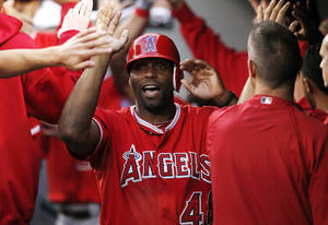 photo -   FILE - This Aug. 31, 2012 file photo shows Los Angeles Angels' Torii Hunter being congratulaed in the dugout during a baseball game against the Seattle Mariners in Seattle. A person with knowledge of the negotiations says free agent outfielder Hunter has agreed to a two-year deal with the Detroit Tigers. The person, who spoke Wednesday, Nov. 14, 2012, on condition of anonymity because no announcement has been made, says the deal is pending a physical. (AP Photo/Elaine Thompson, File)