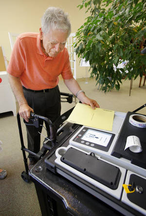 photo - John Boaz, Edmond, putting his ballot in the voting machine at precinct 47 in Edmond Tuesday, June 26, 2012.   Photo by Paul B. Southerland, The Oklahoman