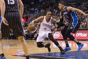 Photo - Oklahoma City Thunder's Russell Westbrook (0) dribbles up the middle of the key while defended by Orlando Magic's Tobias Harris (12) during the second half of an NBA basketball game on Friday, March 22, 2013, in Orlando, Fla. The Oklahoma City Thunder won 97-89.  (AP Photo/Willie J. Allen Jr.) ORG XMIT: FLWA108