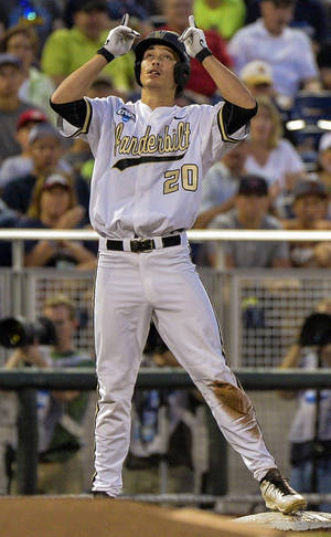 Photo - Vanderbilt's Bryan Reynolds (20) gestures at third base after hitting a triple that scored Dansby Swanson in the fourth inning of an NCAA baseball College World Series game in Omaha, Neb., Saturday, June 14, 2014. (AP Photo/Ted Kirk)
