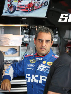 Photo - Driver Juan Pablo Montoya is seen in the garage before a practice session for the NASCAR Sprint Cup series Quicken Loans 400 auto race at Michigan International Speedway in Brooklyn, Mich., Friday, June 13, 2014. Montoya will compete in his first NASCAR race of the season, a tuneup for next month's Brickyard 400. (AP Photo/Bob Brodbeck)