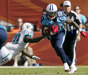 photo -   Tennessee Titans running back Chris Johnson (28) runs past Miami Dolphins safety Reshad Jones (20) during the second quarter of their NFL football game, Sunday, Nov. 11, 2012, in Miami. The Titans won 37-3. (AP Photo/The Miami Herald, Joe Rimkus Jr.) MAGS OUT