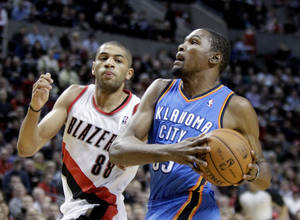 Photo - Oklahoma City Thunder forward Kevin Durant, right, drives to the basket on a fast break past Portland Trail Blazers forward Nicolas Batum, from France, during the first half of an NBA basketball game in Portland, Ore., Wednesday, Dec. 4, 2013. (AP Photo/Don Ryan)