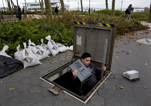 Photo -   A technician with the Battery Conservancy removes below-ground fountain operation equipment near the water's edge at Battery Park in New York, Sunday, Oct. 28, 2012. Areas in the Northeast are preparing for the arrival of Hurricane Sandy and a possible flooding storm surge. (AP Photo/Craig Ruttle)