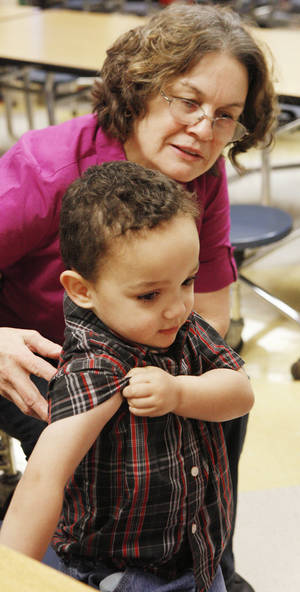 Photo - Anthanetta Smith watches Wednesday as her son Montese Jenkins, 3, rolls up his sleeve to get a flu shot at Mark Twain Elementary School. Photo by Paul B. Southerland, The Oklahoman <strong>PAUL B. SOUTHERLAND</strong>