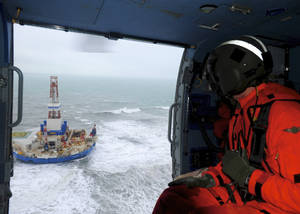 photo - This aerial image provided by the U.S. Coast Guard shows Rear Adm. Thomas Ostebo, Incident Management Team commander, observing the Royal Dutch Shell drilling rig Kulluk aground during an overflight off a small island near Kodiak Island Tuesday Jan. 1, 2013. No leak has been seen from the drilling ship that grounded off the island during a storm, officials said Wednesday, as opponents criticized the growing race to explore the Arctic for energy resources. (AP Photo/U.S. Coast Guard, Sara Francis)