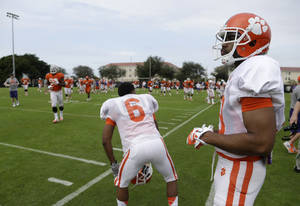 Photo - Clemson quarterback Tajh Boyd, right, stands on the field during college football practice Monday, Dec. 30, 2013, at Barry University in Miami Shores, Fla. Clemson plays Ohio State in the Orange Bowl Jan. 3. (AP Photo/Lynne Sladky)