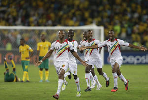 photo - Mali players, including captain Seydou Keita, front, celebrate as they defeat host nation South Africa on penalties in their African Cup of Nations quarterfinal soccer match, at Moses Mabhida Stadium in Durban, South Africa, Saturday, Feb. 2, 2013. (AP Photo/Rebecca Blackwell)