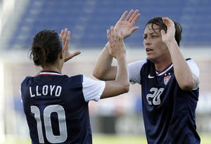Photo - United State's Abby Wambach (20) high-fives teammate Carli Lloyd (10) after Wambach scored against Russia during an international friendly soccer match in Boca Raton, Fla., Saturday, Feb. 8, 2014. The U.S. won 7-0. (AP Photo/Alan Diaz)