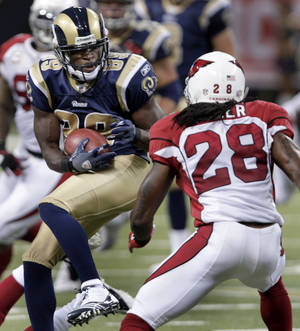 Photo - St. Louis Rams wide receiver Mark Clayton, left, catches a 5-yard pass as Arizona Cardinals cornerback Greg Toler defends during the second quarter of an NFL football game Sunday, Sept. 12, 2010, in St. Louis. (AP Photo/Tom Gannam) ORG XMIT: MOJR117