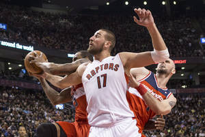 Photo - Toronto Raptors' Jonas Valanciunas, center, battles for a rebound with Washington Wizards' Trevor Booker, left, and Marcin Gortat during first half NBA basketball action in Toronto, Thursday, Feb. 27, 2014. (AP Photo/The Canadian Press, Chris Young)