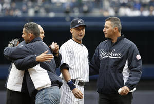 Photo - From left, former New York Yankees relief pitcher Mariano Rivera, former Yankees catcher Jorge Posada, New York Yankees shortstop Derek Jeter and former New York Yankees starting pitcher Andy Pettitte embrace after Rivera and Pettitte threw out the ceremonial first pitches to Posada and Jeter before the Yankees home opening baseball game against the Baltimore Orioles, at Yankee Stadium in New York, Monday, April 7, 2014.  (AP Photo/Kathy Willens)